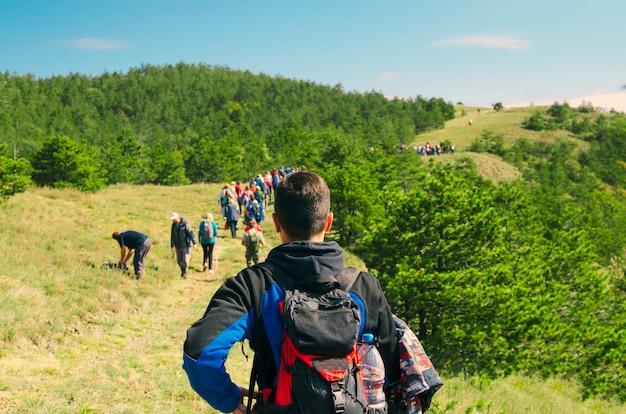 山の緑の丘の上を歩いてハイキングする人々のグループ。活動的なライフスタイルとチームbu