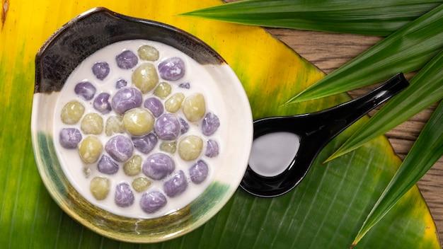 ブアローイ、ブアローイ、ブアローイ、ブアローイ、タイのデザート、甘いココナッツミルクのもち米の餃子、タロの紫色、バナナの葉のパンダンの葉の緑色、上面図、フルhd比