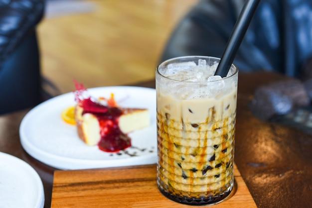 Пузырьковый чай с молоком в стакане на деревянном столе с тортом