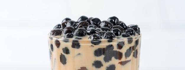 Пузырьковый чай с молоком с жемчужной начинкой из тапиоки, знаменитый тайваньский напиток на фоне белого деревянного стола в стакане, крупным планом, копией пространства