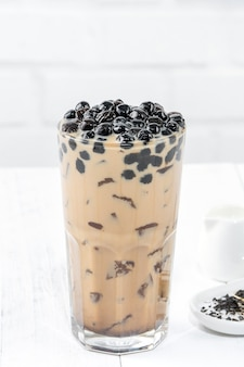 Bubble milk tea with tapioca pearl topping, famous taiwanese drink on white wooden table background in drinking glass, close up, copy space