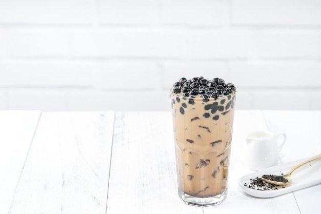Bubble milk tea with tapioca pearl topping, famous taiwanese drink on white wooden table