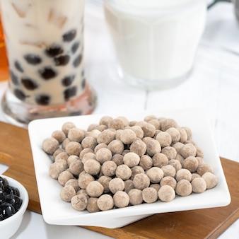 タピオカパールのトッピング成分とバブルミルクティー、グラスを飲む白い木製のテーブルの背景に有名な台湾の飲み物、クローズアップ、コピースペース
