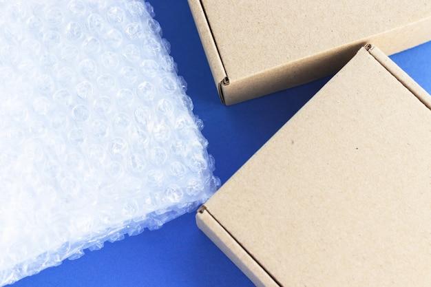 Пузырьковая пленка и картонные коробки. прозрачный пластиковый материал для упаковки хрупких предметов. безопасная доставка, интернет-магазины. вид сверху, плоская планировка, синий фон.