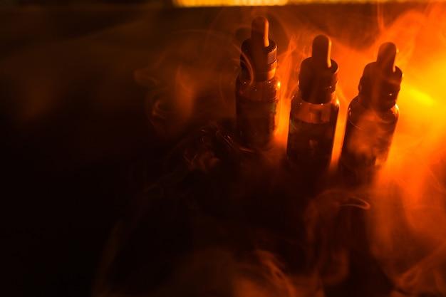 Пузырьки жидких бутылок на темном фоне с дымом и оранжевым светом. фон vape.