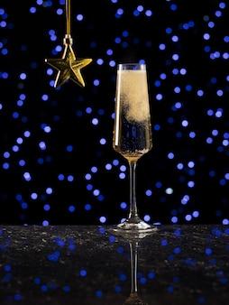 Бурлящее игристое вино в стакане на фоне синих огней боке. популярный алкогольный напиток.