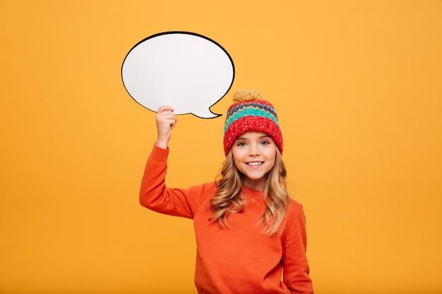 Улыбающаяся молодая девушка в свитере и шляпе, держащей пустую речь buble и смотрящей на камеру над апельсином