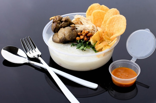 Bubur ayam or indonesian rice  porridge with shredded chicken. served with kerupuk (cracker), fried soy bean, chicken liver, and sambal. isolated on black background. concept food on the go packaging