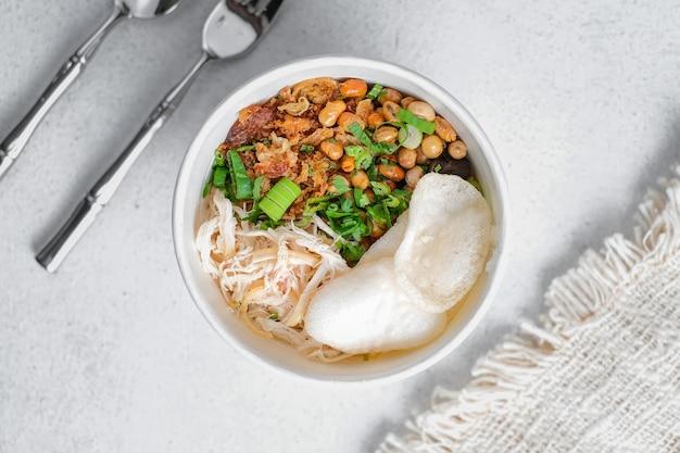 Bubur ayam, indonesian rice porridge with shredded chicken over white background