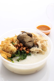 Bubur ayam or indonesian rice  porridgew with shredded chicken. served with kerupuk (cracker), fried soy bean, chicken liver, and sambal. isolated on white background. concept food on the go