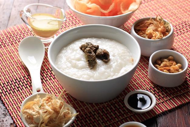Bubur ayam 또는 갈가리 찢긴 닭고기를 곁들인 인도네시아 쌀 죽. kerukpuk (크래커), 간장, 튀긴 콩, 삼발과 함께 제공