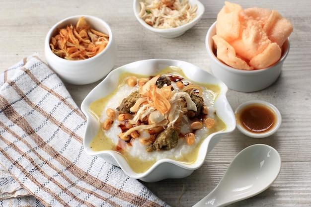갈가리 찢긴 닭고기를 곁들인 bubur ayam 또는 인도네시아 쌀 죽. kerukpuk (크래커), 간장, 튀긴 콩, 삼발과 함께 제공