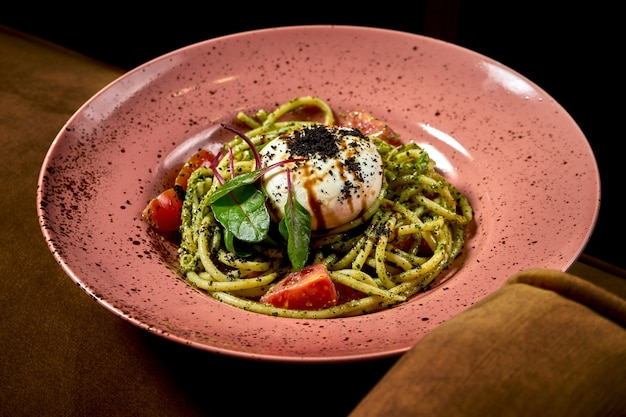Букатини, итальянские спагетти с помидорами, соусом песто и сыром буррата, подаются на тарелке. ресторанная еда. вид сверху. итальянская кухня