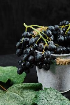 Un secchio di uva nera con foglie su sfondo nero. foto di alta qualità