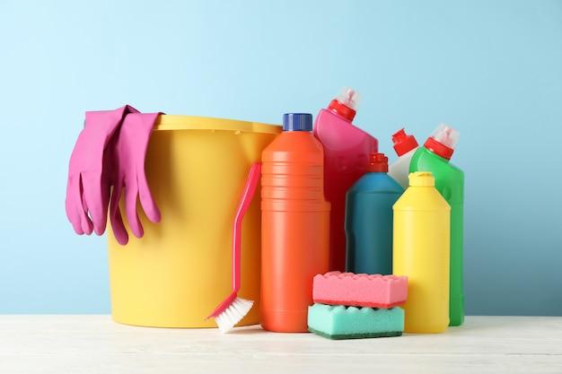 Ведро, бутылки с моющими и чистящими средствами на синем фоне, место для текста