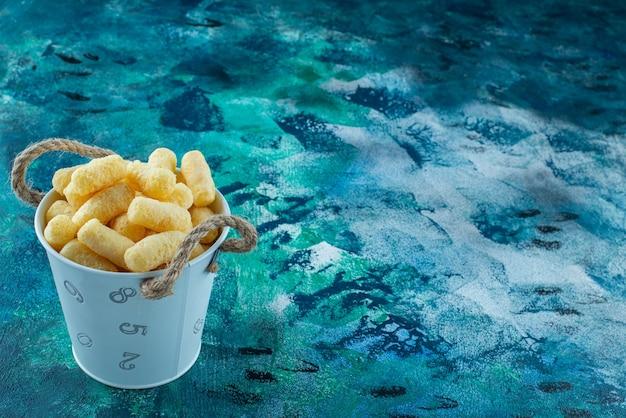 A bucket of corn sticks on the marble surface
