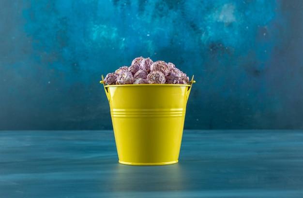 Secchio di caramelle di popcorn viola croccanti su sfondo blu. foto di alta qualità