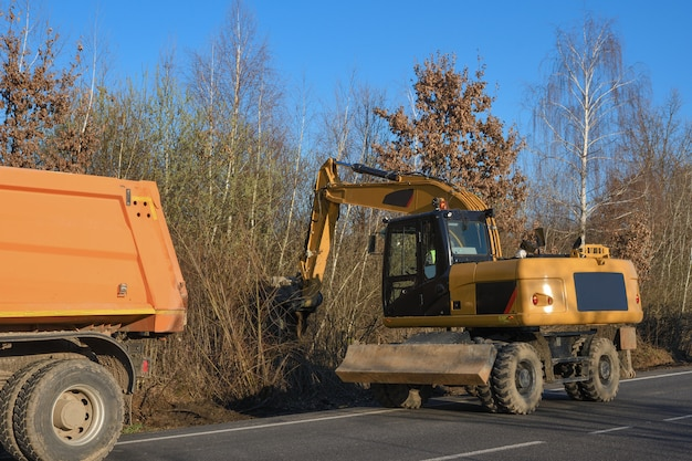 A bucket excavator clears the roadside. road works. laying a new road. loading excavator clay and stones