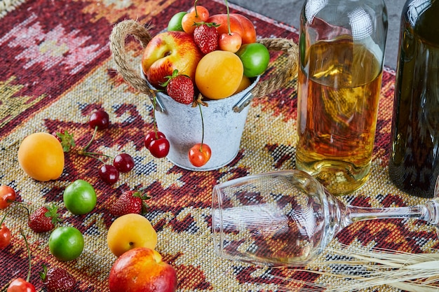 Bucket of fresh summer fruits, bottle of white wine and empty glass on carved rug.