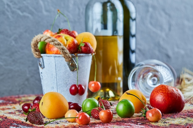 Bucket of fresh summer fruits, bottle of white wine and empty glass on carved rug
