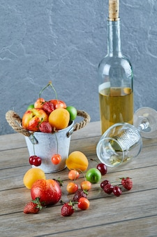 Bucket of fresh summer fruits, bottle of white wine and empty glass on wooden table.