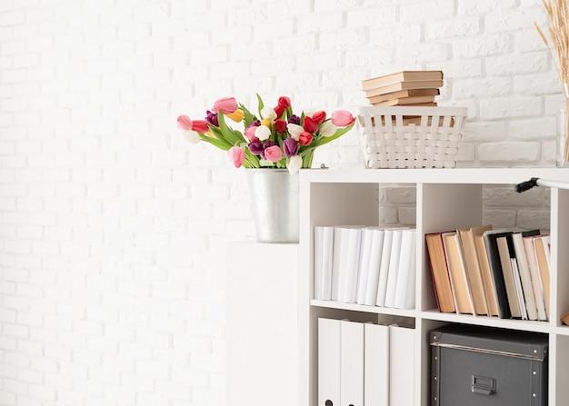 Bucket of fresh tulip flowers next to the bookshelf over white brick wall background