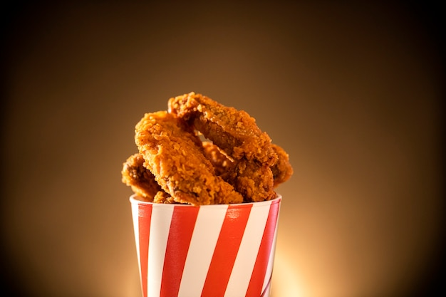 Bucket full of crispy kentucky fried chicken with smoke on brown background. selective focus.