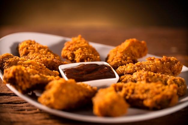 갈색 배경에 연기와 바베큐 소스와 함께 바삭한 켄터키 프라이드 치킨의 전체 양동이. 선택적 초점.