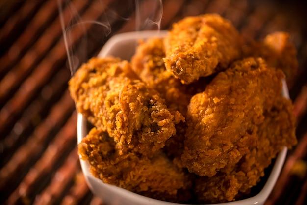 갈색 바탕에 연기와 바삭한 켄터키 프라이드 치킨의 전체 양동이. 선택적 초점.