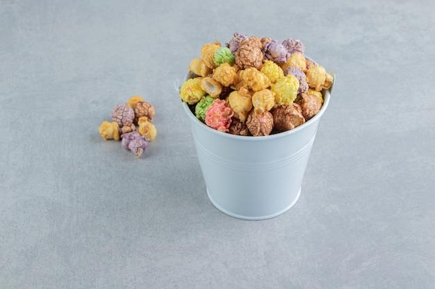 Un secchio pieno di dolci popcorn multicolori.