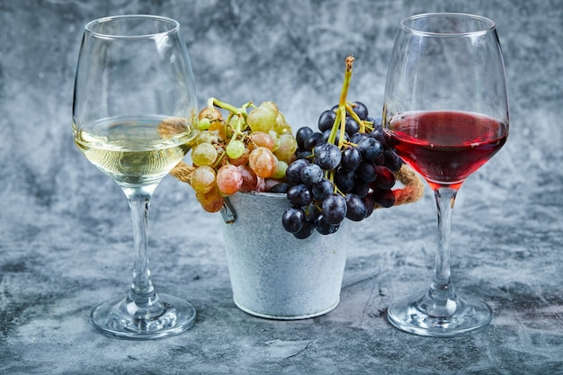 Bucket of grapes and glasses of wine on marble background
