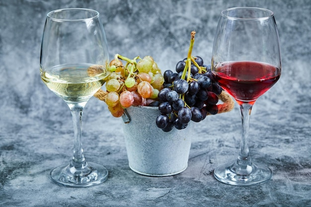 Bucket of grapes and glasses of wone on marble.