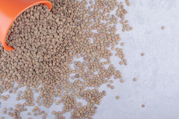 갈색 렌즈 콩 양동이가 대리석 표면 전체에 쏟아졌습니다.