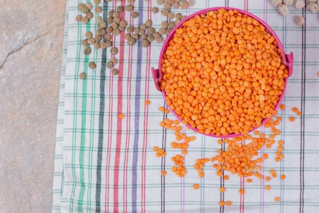 テーブルクロスに乾燥した赤レンズ豆のバケツ。