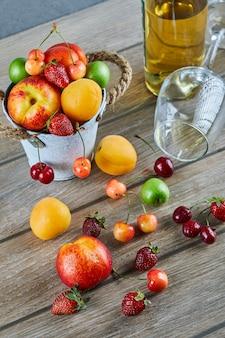 新鮮な夏の果物のバケツ、白ワインのボトルと木製のテーブルの上の空のガラス。