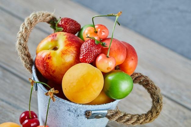 나무 테이블에 신선한 여름 과일 양동이입니다.