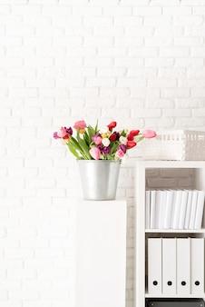 Ведро свежих тюльпанов рядом с книжной полкой на фоне белой кирпичной стены