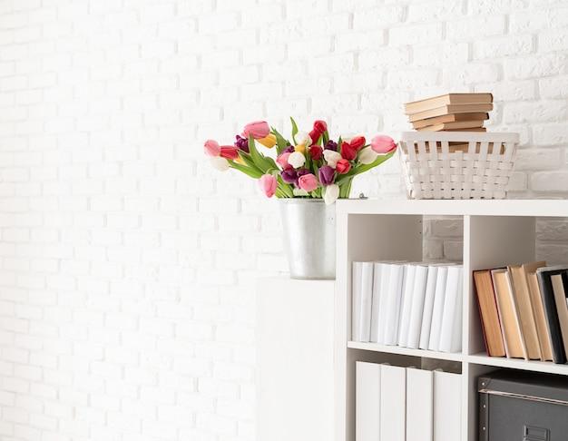 白いレンガの壁の背景の上の本棚の横にある新鮮なチューリップの花のバケツ