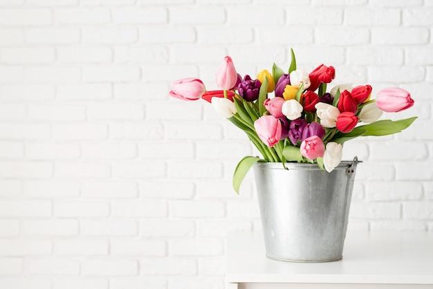 白いレンガの壁の背景に新鮮なチューリップの花のバケツ