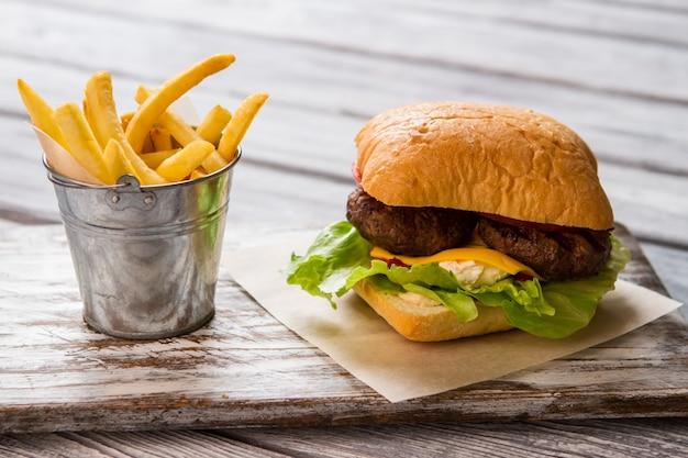 햄버거 근처 감자 튀김 양동이입니다. 양상추와 구운 고기. 로컬 비스트로에서 스낵. 갓 구워낸 치즈버거.