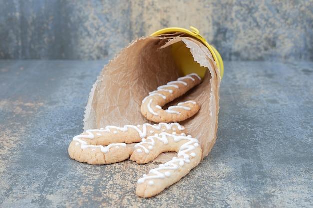 大理石のテーブルにジンジャーブレッドクッキーのバケツ。高品質の写真