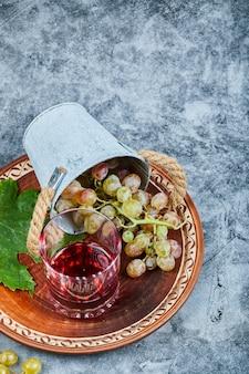Ведро винограда и стакан сока на мраморе.