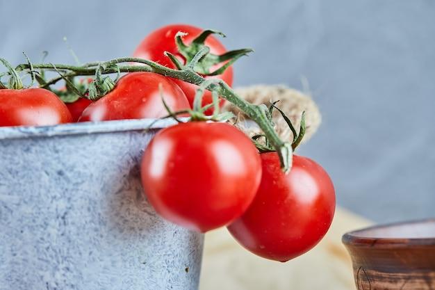 木製のテーブルの上の赤いジューシーなトマトのバケツ。