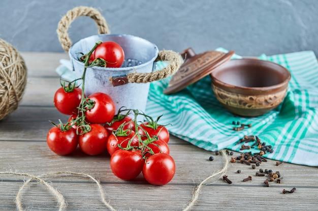 空のボウルと木製のテーブルの上のトマトとクローブのバケツ