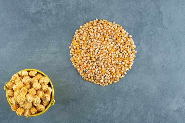 Bucket of popcorn candy next to a round pile of corn grain on marble background. high quality photo