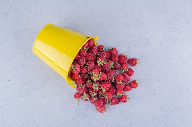 Bucket of raspberries spilled over on marble background.