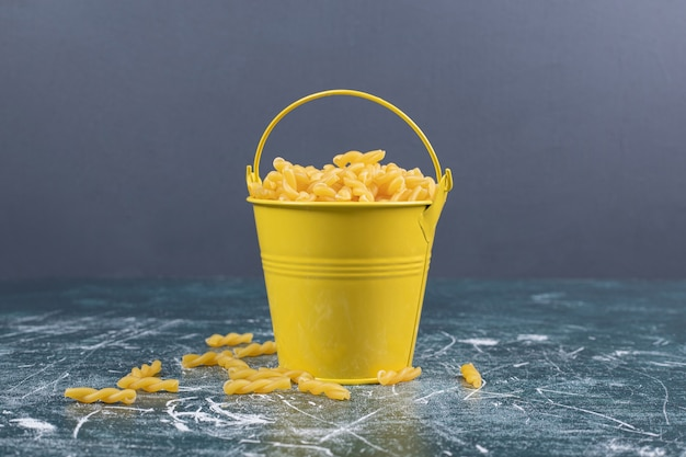 Bucket of raw spiral pasta on blue background. high quality photo