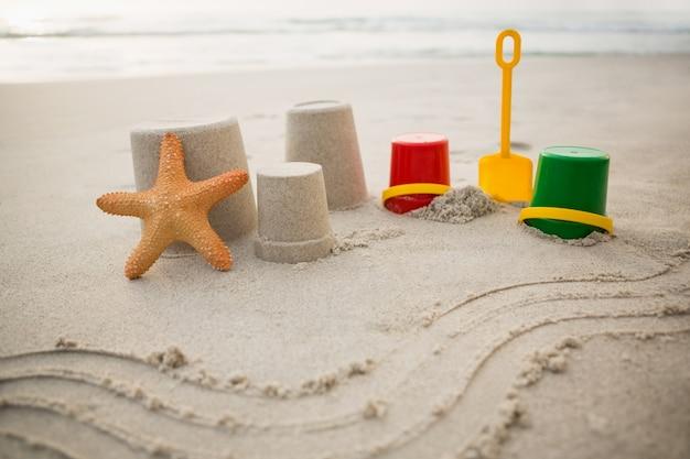 Bucket, spade, starfish and sand castles on beach