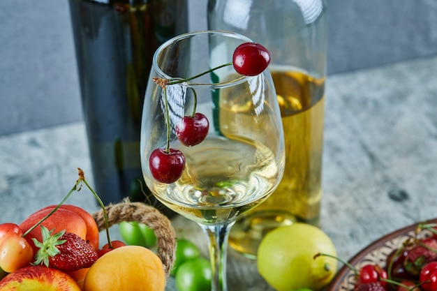 Bucket of summer fruits, lemon and a glass of white wine on marble surface