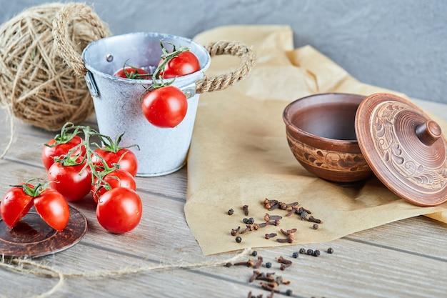 Secchio di pomodori e pomodoro tagliato a metà sulla tavola di legno con ciotola vuota